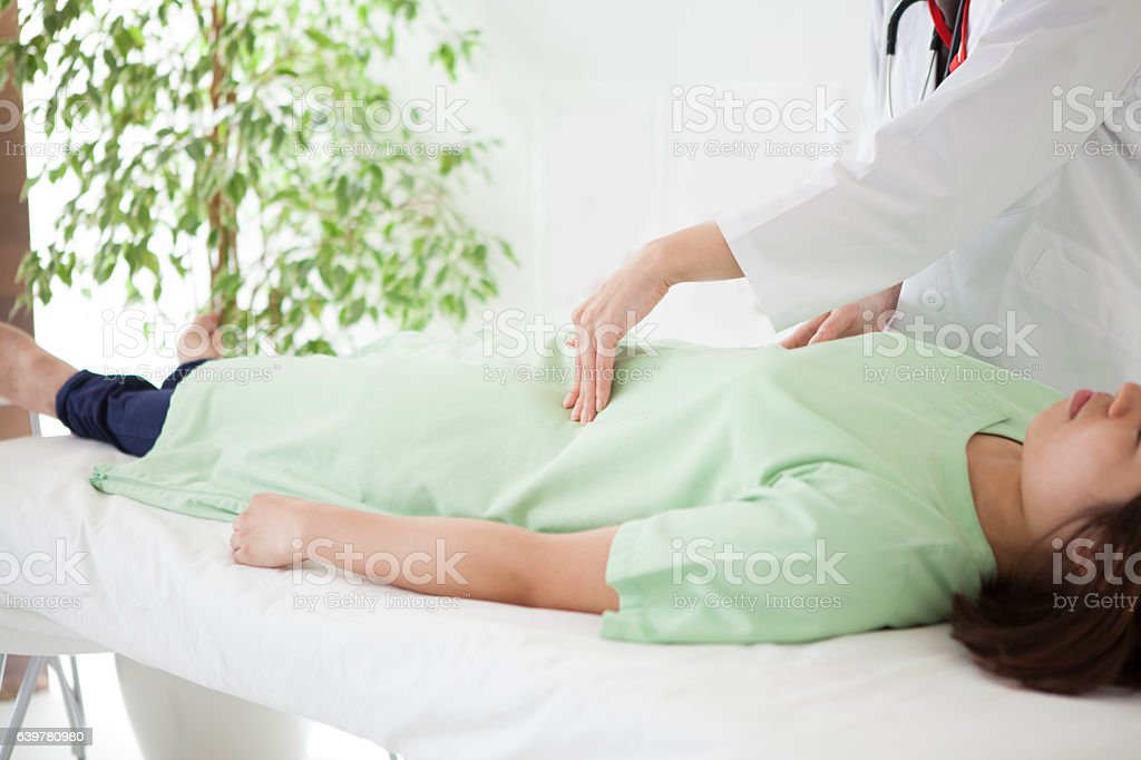 Doctor massaging the patient's gastrointestinal tract stock photo