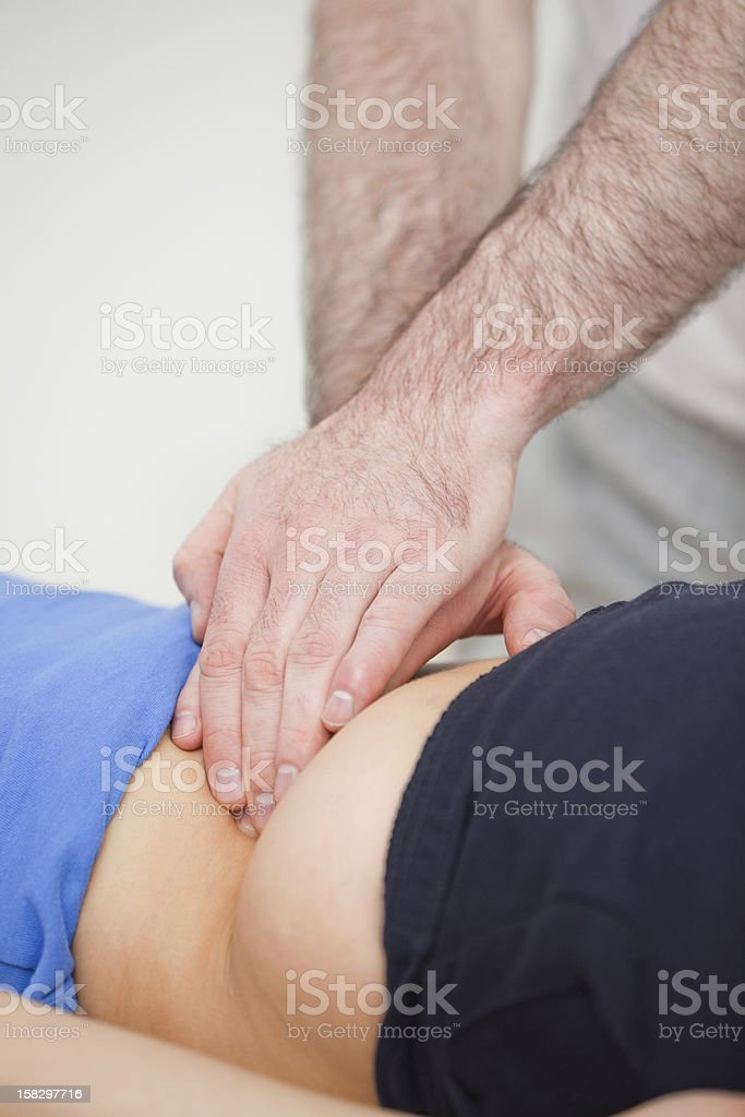 Doctor massing the lower back of a woman royalty-free stock photo