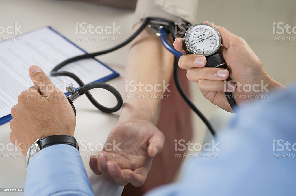 Doctor Measures Pressure In The Patient stock photo