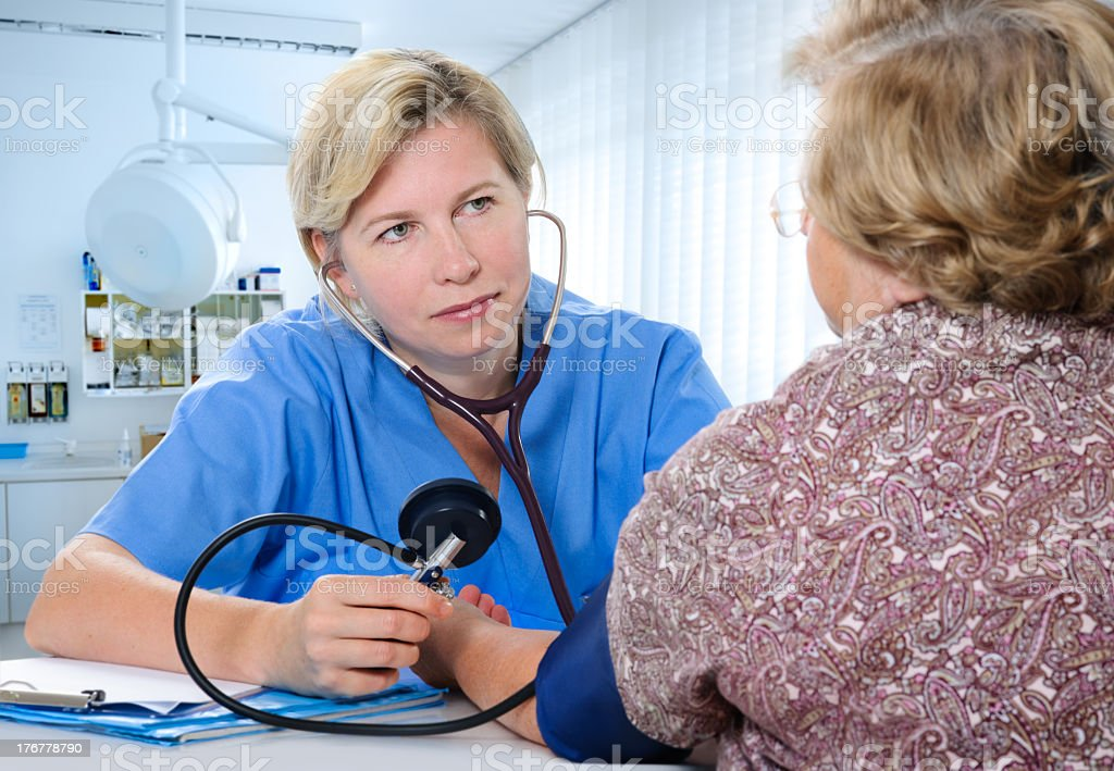 A doctor measuring a patients blood pressure royalty-free stock photo