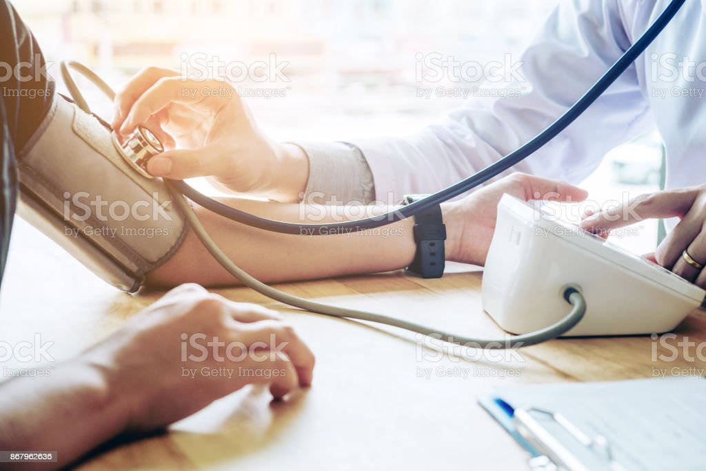 Doctor Measuring arterial blood pressure woman patient on arm Health care in hospital stock photo