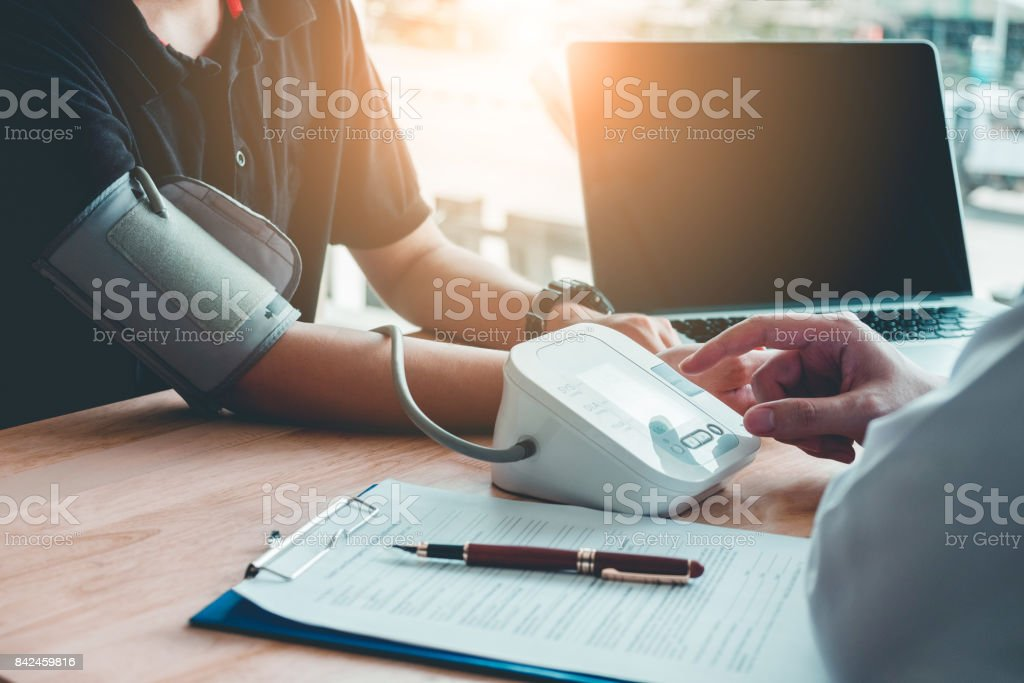 Doctor Measuring arterial blood pressure woman patient on right arm Health care in hospital stock photo