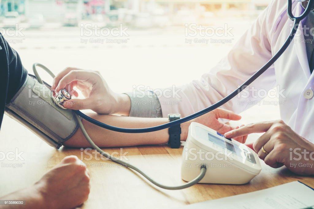 Médico mide la presión arterial paciente de mujer en brazo derecho la atención en el hospital - foto de stock