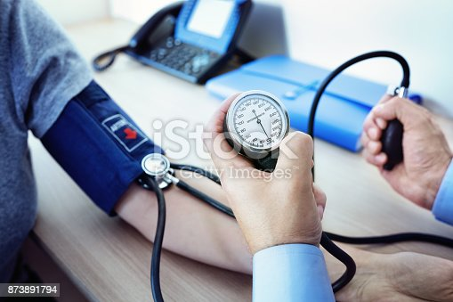 istock Doctor measuring blood pressure of patient 873891794