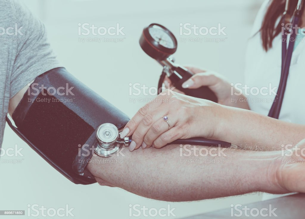 Doctor measuring blood pressure stock photo