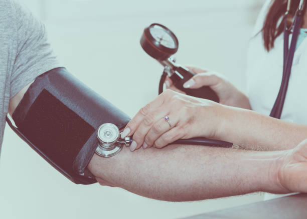 Doctor measuring blood pressure Doctor measuring blood pressure of patient hypertensive stock pictures, royalty-free photos & images