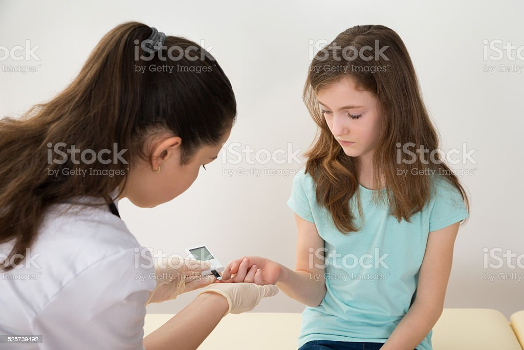 Doctor Measuring Blood Sugar Level Of Girl stock photo