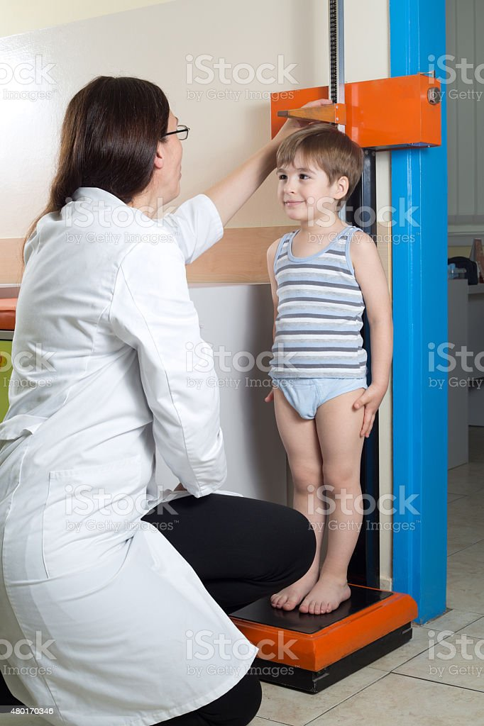 Doctor Measuring Height of Little Boy on Traditional Medical Scale stock photo