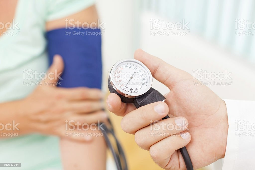 Doctor measuring patient blood pressure stock photo