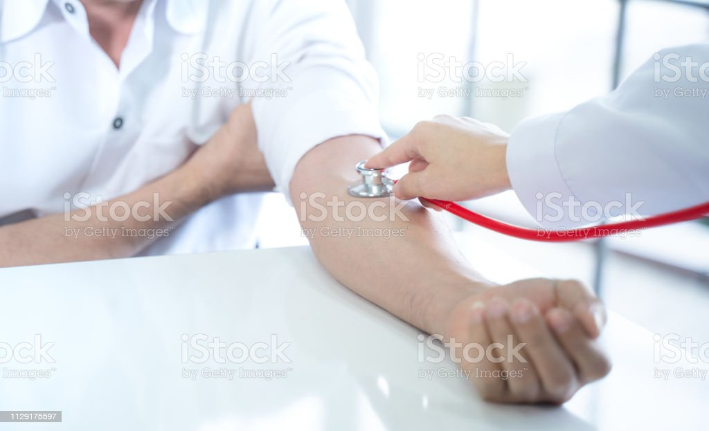 Doctor Measuring Patients Blood Pressure Stock Photo - Download