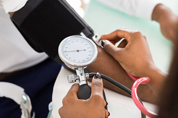 Doctor Measuring Patients Blood Pressure Close-up Of Doctor Measuring Patients Blood Pressure With Stethoscope hypertensive stock pictures, royalty-free photos & images