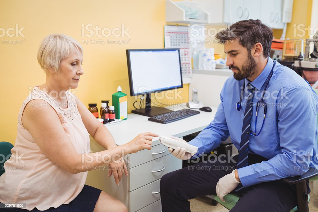 Doctor measuring sugar level of patient with glucometer stock photo