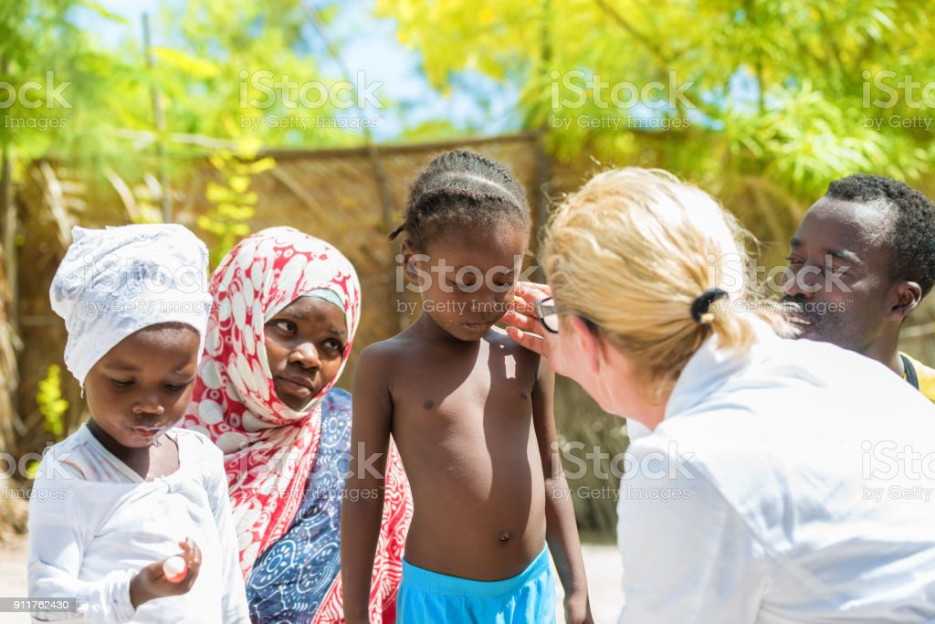 Doctor meet African child Caucasian female doctor meeting African family with a children.Doctor touching little girl's face Adult Stock Photo