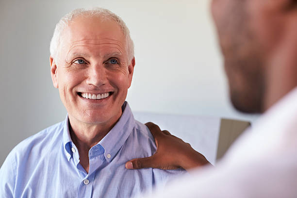 Doctor Meeting With Mature Male Patient In Exam Room stock photo