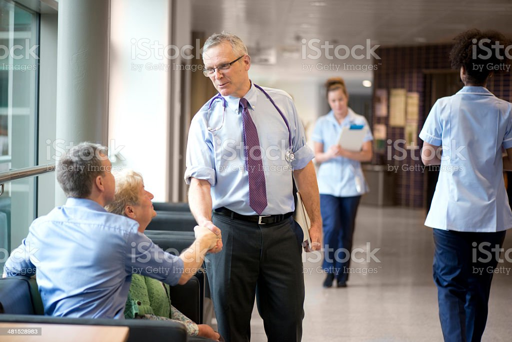 Doctor meets two people at clinic stock photo