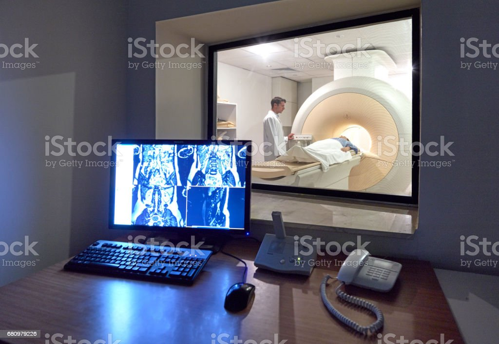 Doctor monitoring CAT scan procedure stock photo