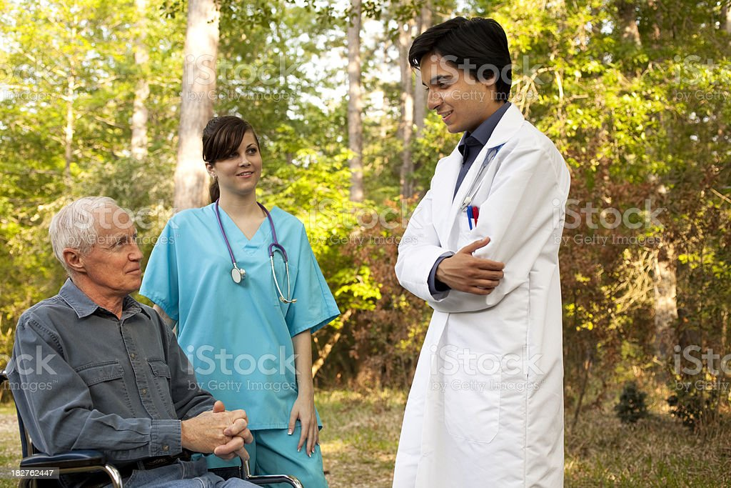 Doctor, nurse and patient in wheel chair outside enjoying weather royalty-free stock photo