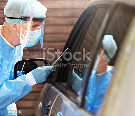 Medical worker about to take a nasal swab from an unseen person in a car to test for coronavirus.