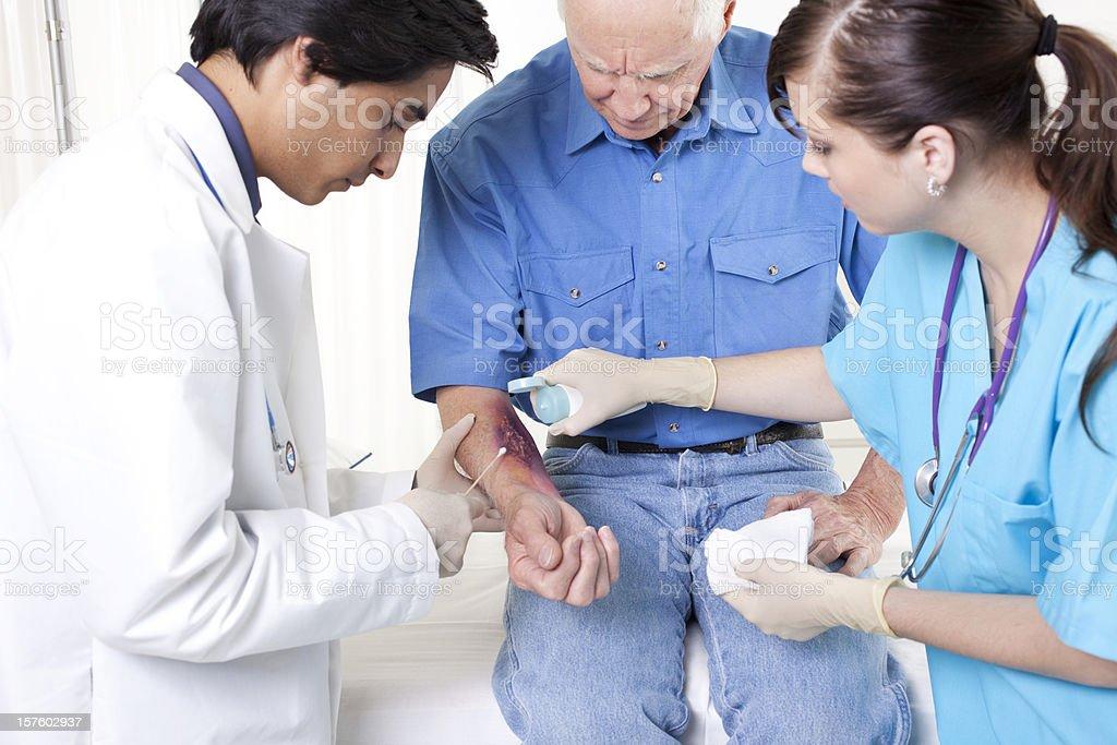 Doctor, nurse treating man's wound, burn.  Emergency room hospital. stock photo