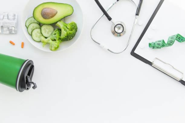 arzt ernährungs-tabelle. gesundes und gesundes essen, brokkoli, pflücker und acado. stethoskop und diät-pillen. top ansicht und flatlay, freier platz für text - ernährungsberater stock-fotos und bilder