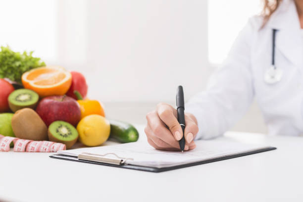 Doctor nutritionist writing on paperwork in office stock photo