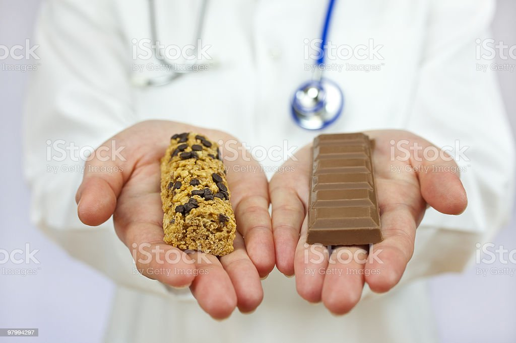 Doctor Offering Choice of Granola Bar and Chocolate royalty-free stock photo