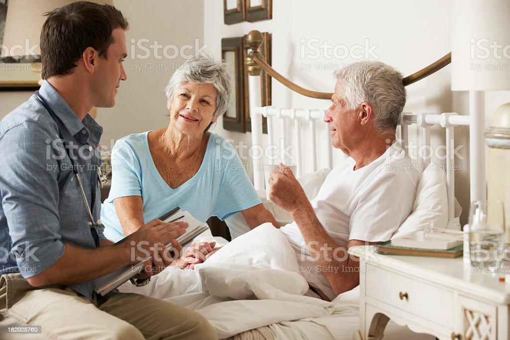 Doutor em visita a uma casa sobre a saúde do paciente sênior masculino - foto de acervo