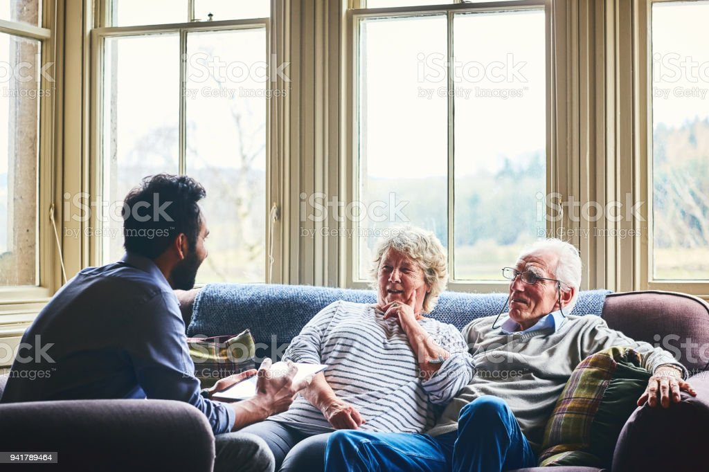 Community doctor on home visit discussing health of senior people...