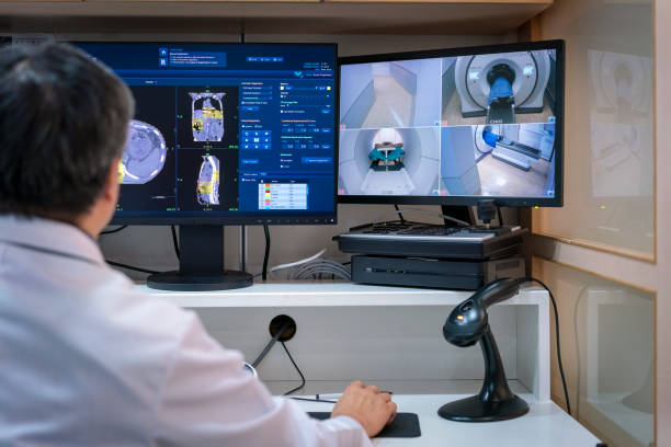 Doctor operating MRI scanner on computer stock photo