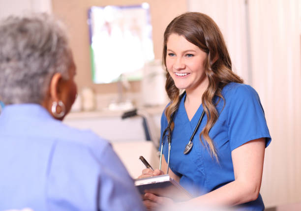 Doctor or nurse and senior adult patient in office, clinic. stock photo