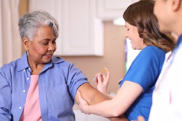 Doctor or nurse gives vaccine to senior adult patient in clinic. Doctor or nurse gives vaccine or medicine injection to senior adult African descent patient in office or clinic setting.  She uses syringe.  Medical exam, consultation, therapist. covid-19 stock pictures, royalty-free photos & images