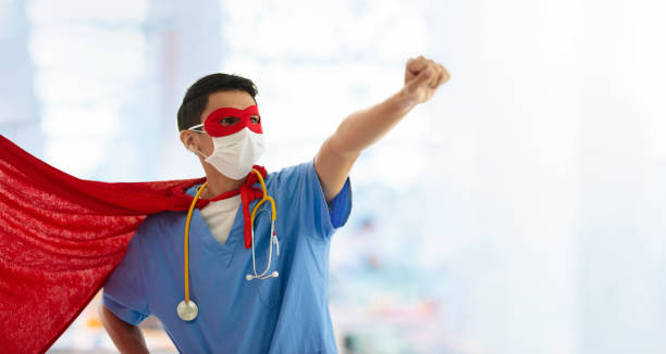 Doctor or nurse in face mask and superhero cape. stock photo