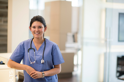 A doctor (dentist, or nurse) posing for a picture in a professional medical office setting with a stethoscope .