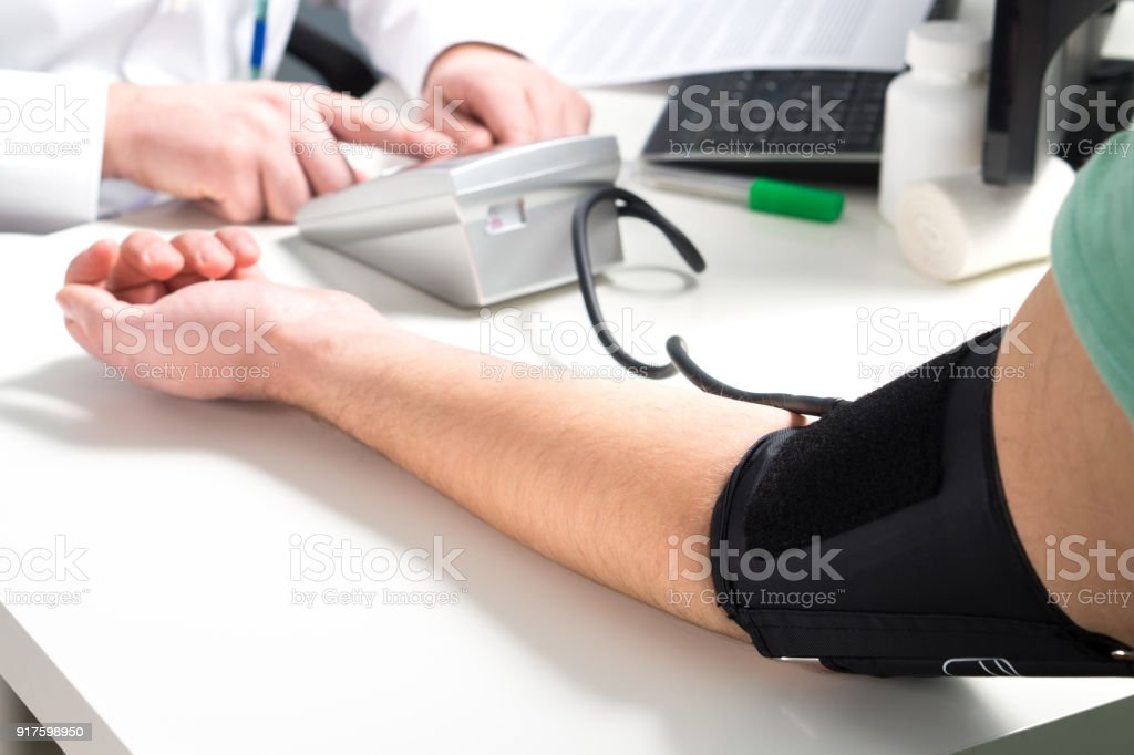 Doctor or nurse measure blood pressure of a patient with meter and monitor device. Hand and arm on emergency room or hospital office table for control, test and examination. stock photo