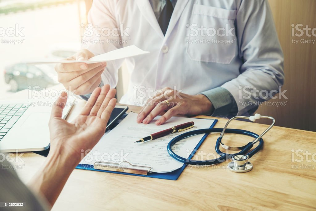 Doctor or physician writing diagnosis and giving a medical prescription to female Patient - foto stock