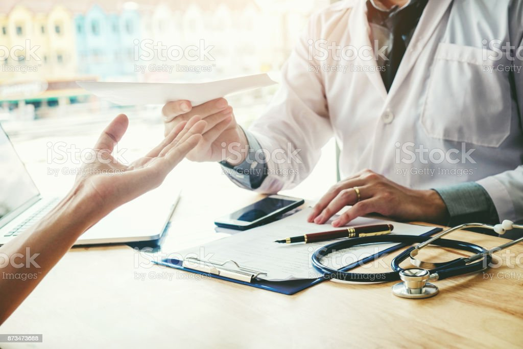 Doctor or physician writing diagnosis and giving a medical prescription to female Patient stock photo