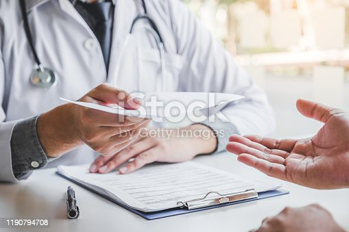 Doctor or physician writing diagnosis and giving a medical prescription to male Patient