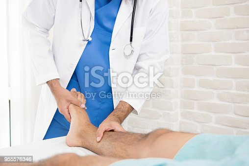 istock Doctor or physiotherapist giving treatment to broken leg patient 955576346