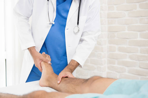 doctor or physiotherapist giving treatment to broken leg patient - caviglia foto e immagini stock