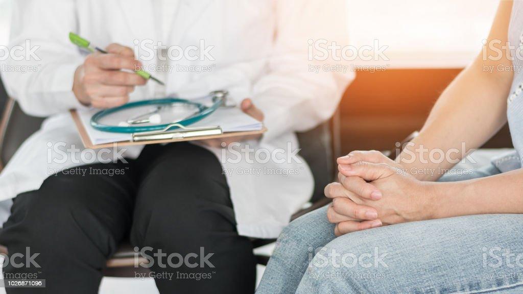 Doctor or psychiatrist consulting and diagnostic examining stressful woman patient on obstetric - gynecological female illness, or mental health in medical clinic or hospital healthcare service center stock photo