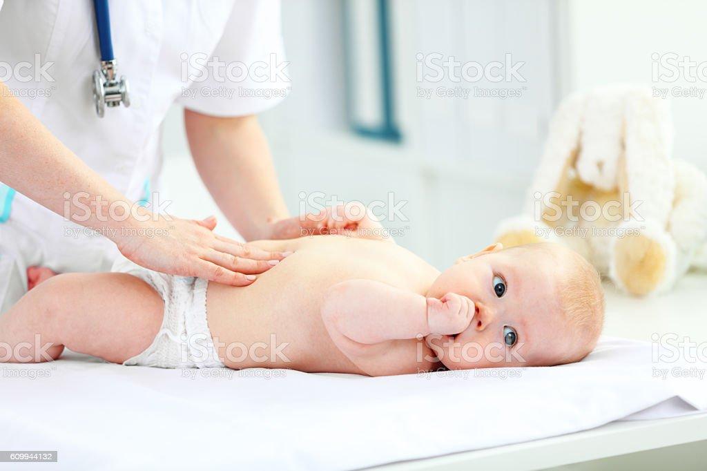 Doctor pediatrician examines baby tummy stock photo