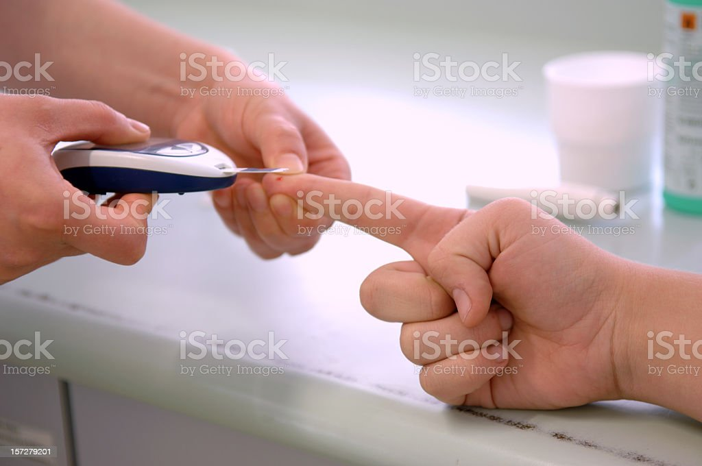 Doctor performing a blood sugar test on a patient royalty-free stock photo
