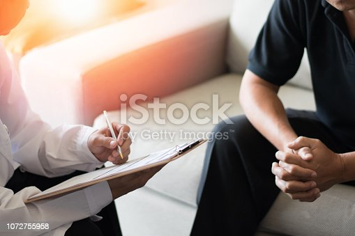Doctor physician consulting with male patients in hospital psychology clinic exam room. Men's health and psychotherapy concept.