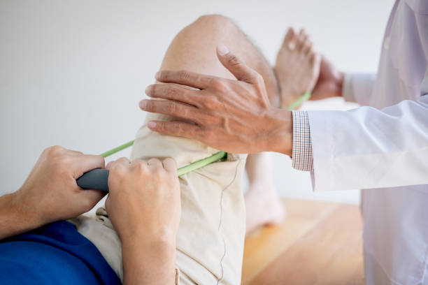 doctor physiotherapist assisting a male patient while giving exercising treatment on stretching his leg on bed in the clinic - sports medicine stock pictures, royalty-free photos & images