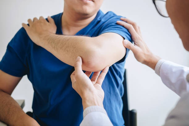 doctor physiotherapist assisting a male patient while giving exercising treatment massaging the arm of patient in a physio room, rehabilitation physiotherapy concept - sports medicine stock pictures, royalty-free photos & images
