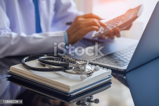 Female doctor or practitioner using calculator and work on laptop computer with medical stethoscope  and notebookon the desk at clinic or hospital. Medical healthcare costs ,fees and revenue concept.