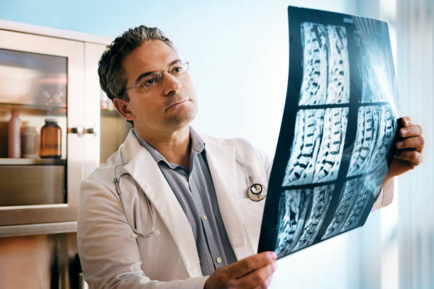 Doctor Doctor looking at MRI of spinal cord. paralysis stock pictures, royalty-free photos & images