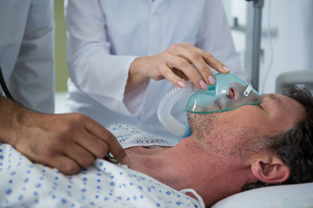 Doctor placing an oxygen mask on the face of a patient Doctor placing an oxygen mask on the face of a patient in hospital oxygen mask stock pictures, royalty-free photos & images