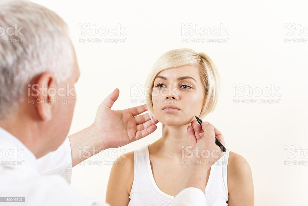 doctor plastic surgeon with patient examine woman, draw on face stock photo