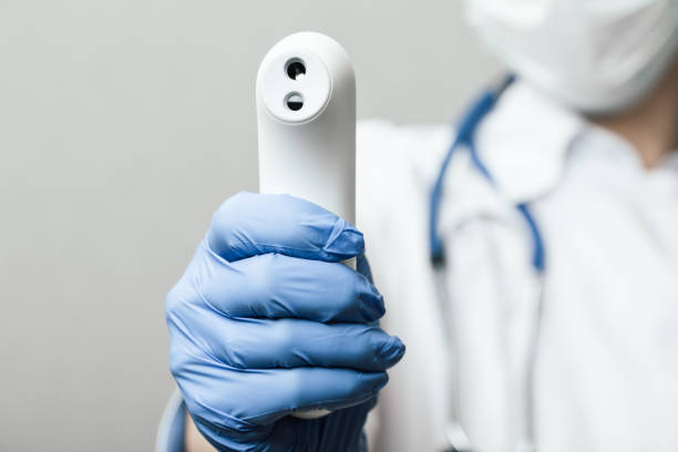 Doctor pointing infrared thermometer gun to check body temperature epidemic virus outbreak concept stock photo